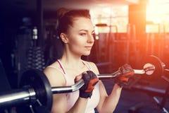 Bíceps bonito novo do treinamento da mulher com barbell fotografia de stock