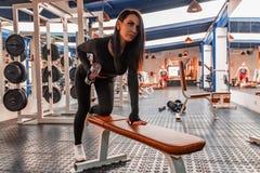 Bíceps bonito novo dos trens da mulher no gym moderno foto de stock
