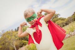 Bíceps de contratación del traje del super héroe de la niña que lleva Imagen de archivo