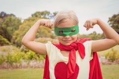 Bíceps de contratación del traje del super héroe de la niña que lleva Imagen de archivo libre de regalías
