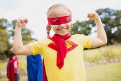 Bíceps de contratación del traje del super héroe de la niña que lleva Fotos de archivo libres de regalías