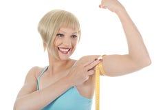 Bíceps de medición de la muchacha atlética hermosa. Fotos de archivo