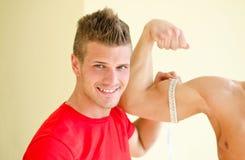 Bíceps de medición del cliente del instructor personal con el metro de la cinta Foto de archivo