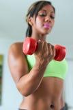 Bíceps home do treinamento da mulher negra da aptidão com pesos Imagens de Stock