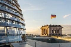 Bóveda de cristal de Reichstag del parlamento en Berlín (el Parlamento alemán) con la bandera alemana Fotografía de archivo