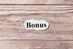 BÔNUS da palavra no papel Conceito Palavras do BÔNUS em um fundo de madeira imagens de stock royalty free
