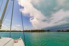 Bö-Linie nähert sich dem Segelboot, das nahe Insel verankert wird Lizenzfreie Stockfotos