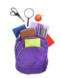 Böcker, äpple, loupe, ryggsäck och blyertspennor som isoleras på vit Royaltyfri Fotografi