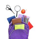 Böcker, äpple, loupe, ryggsäck och blyertspennor som isoleras på vit Fotografering för Bildbyråer