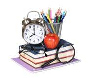 Böcker, äpple, ringklocka och blyertspennor som isoleras på vit Royaltyfria Foton