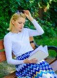 Böcker är hennes passion Parkerar det blonda tagandeavbrottet för kvinnan som in kopplar av, läseboken Flickan sitter bänken som  arkivbild