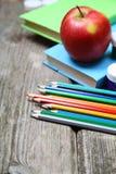 Böcker, blyertspennor och ett äpple Fotografering för Bildbyråer