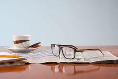 Böcker, exponeringsglas och kopp kaffe på en trätabell Royaltyfri Fotografi