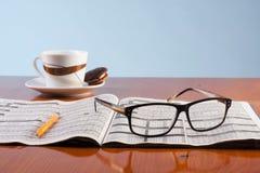 Böcker, exponeringsglas och kopp kaffe på en trätabell Royaltyfri Foto