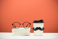 Böcker, exponeringsglas och kopp med mustaschen Royaltyfri Fotografi