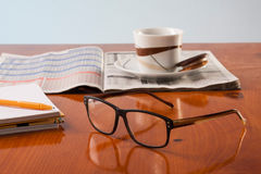 Böcker, exponeringsglas och koppkafé Co på en trätabell Arkivbild