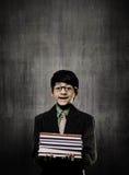 Böcker för snilleLittle Boy innehav som bär exponeringsglas som ler nära C arkivfoton