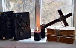 Böcker för svart magi, svartstearinljus och kors mot gammalt fönster Royaltyfri Bild