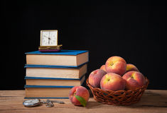 Böcker, gammal klocka och nya persikor Royaltyfri Foto