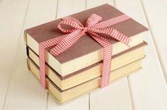 Böcker inbujorde upp i rött band Arkivfoton