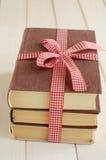 Böcker inbujorde upp i rött band Arkivfoto