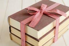Böcker inbujorde upp i rött band Royaltyfri Foto