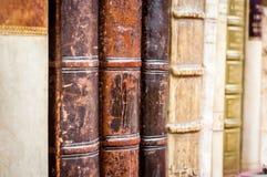böcker isolerad rad Gammalt läder täckte böcker Arkivfoton