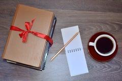 Böcker kaffe och anteckningsbok med blyertspennan arkivbilder
