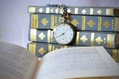 Böcker med den gamla klockan royaltyfria foton