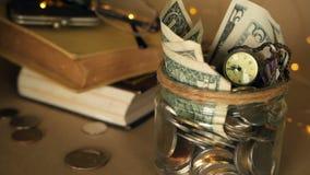 Böcker med den glass encentmyntet skorrar fyllt med mynt och sedlar Skolavgift- eller utbildningsfinansieringbegrepp Stipendiumpe lager videofilmer