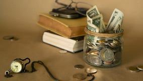 Böcker med den glass encentmyntet skorrar fyllt med mynt och sedlar Skolavgift- eller utbildningsfinansieringbegrepp Stipendiumpe arkivfilmer