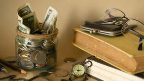 Böcker med den glass encentmyntet skorrar fyllt med mynt och sedlar Skolavgift- eller utbildningsfinansieringbegrepp Stipendiumpe stock video