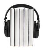 Böcker med hörlurar på isolerat Royaltyfria Bilder