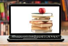 Böcker och äpple på bärbar datorskärmen Fotografering för Bildbyråer