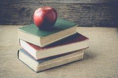 Böcker och äpplet på retro bakgrund med Instagram stil filtrerar Fotografering för Bildbyråer