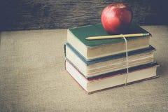 Böcker och äpplet på retro bakgrund med Instagram stil filtrerar Royaltyfria Bilder