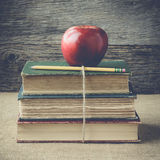 Böcker och äpplet på retro bakgrund med Instagram stil filtrerar Arkivfoto