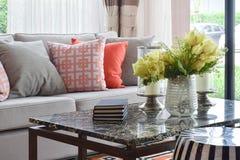 Böcker och dekorativa objekt på marmoröverkanttabellen och den livliga soffan ställde in arkivbilder