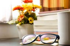 Böcker och exponeringsglasen, near fönster. Arkivfoton
