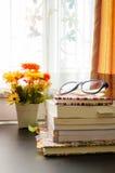 Böcker och exponeringsglasen, near fönster. Royaltyfri Foto