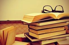Böcker och glasögon i en gammal resväska, med en retro effekt arkivfoto