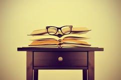 Böcker och glasögon på ett skrivbord, med en retro effekt royaltyfria foton