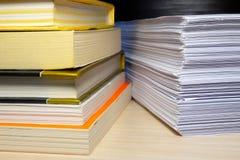 Böcker och legitimationshandlingar på tabellen arkivfoton