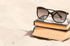 Böcker och solglasögon på en strand Royaltyfria Bilder
