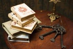 Böcker och tangenter på trätabellen Arkivbilder