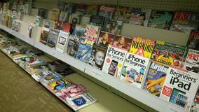 Böcker och tidskrifter på hyllor Arkivbild