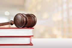 Böcker och träauktionsklubba på tabellen framför den guld- rättvisasockeln för begreppet 3d scalen Arkivbild