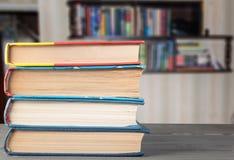 Böcker på tabellen på bakgrunden av en bokhylla arkivbilder