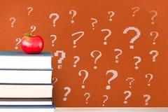 Böcker på tabellen mot den orange svart tavla med frågefläckar arkivbilder