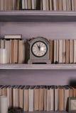 Böcker runt om den gamla klockan Arkivbild